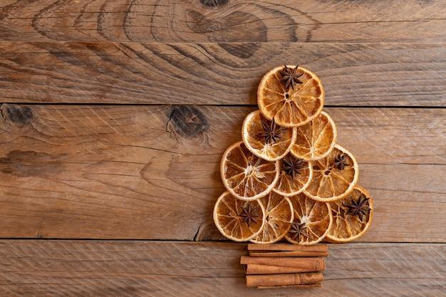 Albero di natale fatto di arance essiccate, cannella e anice. visto dall'alto. concetto di biglietto di auguri per le vacanze di natale. copia spazio per il testo.