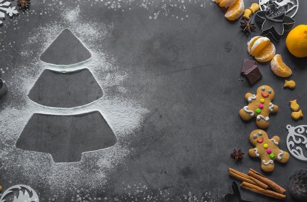 Albero di natale a base di farina sul tavolo scuro con biscotti al cioccolato e cannella tagliabiscotti