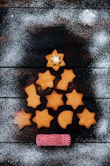 Albero di natale fatto dai biscotti di pan di zenzero sulla vecchia superficie di legno.