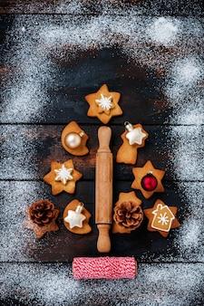 Albero di natale fatto da biscotti di panpepato con giocattoli e nastro rosso sulla vecchia superficie di legno. vista dall'alto