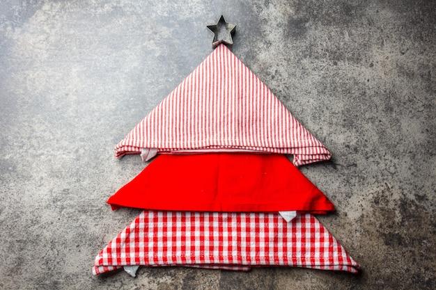 Albero di natale fatto da tovaglioli da cucina e piatto rosso