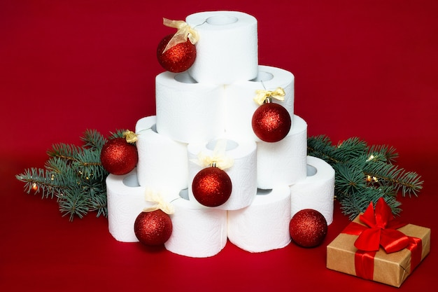 Albero di natale fatto da rotoli di carta igienica decorato con palline lucide vicino a un regalo e rami di abete su fondo rosso