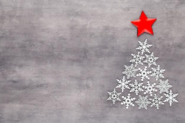 Albero di natale fatto da decorazioni in fiocco di neve bianca su sfondo grigio