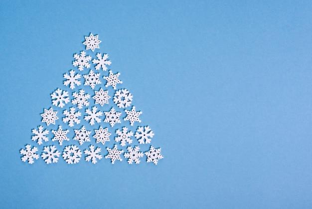 Albero di natale fatto da fiocchi di neve bianchi su sfondo blu