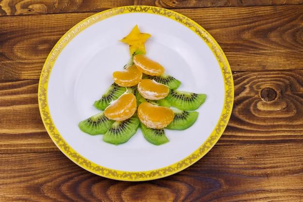 Albero di natale fatto di fette di kiwi e lobuli di mandarino su un tavolo di legno. vista dall'alto. idea creativa per i dolci delle feste di natale e capodanno. idea di cibo divertente per i bambini