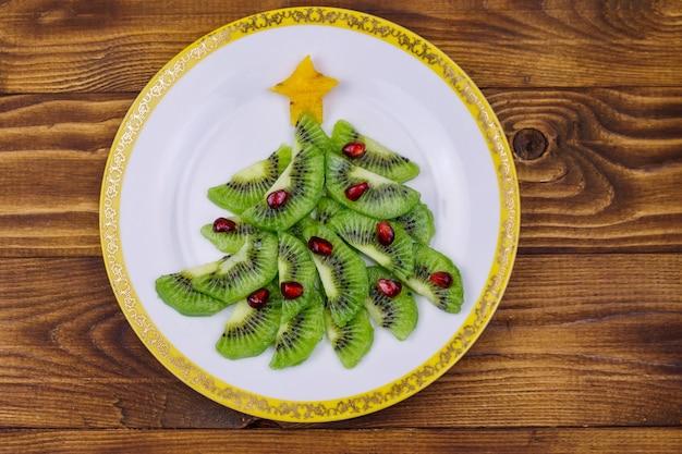 Albero di natale fatto di fette di kiwi e melograno sul tavolo di legno. vista dall'alto. idea creativa per i dolci delle feste di natale e capodanno. idea di cibo divertente per i bambini