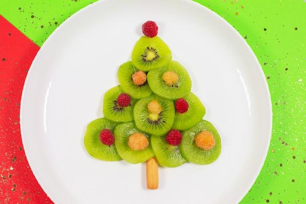 Albero di natale fatto di fette di kiwi tabella dei colori invernali. idea creativa per la colazione di natale o per i dolci festivi di capodanno per bambini. vista dall'alto.