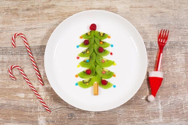 Albero di natale fatto di fette di kiwi sulla tavola di legno. idea creativa per la colazione di natale o per i dolci festivi di capodanno per bambini. vista dall'alto.