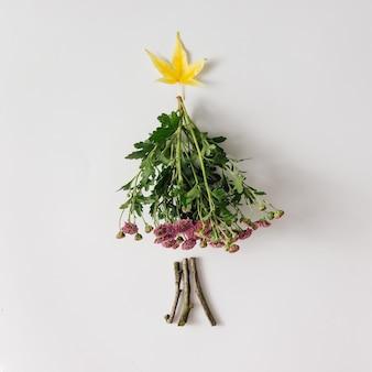 Albero di natale fatto di foglie e fiori.