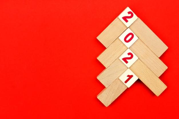 Albero di natale fatto di barre di legno chiaro su sfondo rosso con i numeri 2021. concetto del prossimo anno nuovo