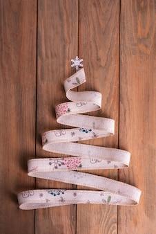 Albero di natale fatto di nastro di lino su uno sfondo di legno. la parte superiore dell'albero è decorata con un fiocco di neve. il concetto di un natale brutale.