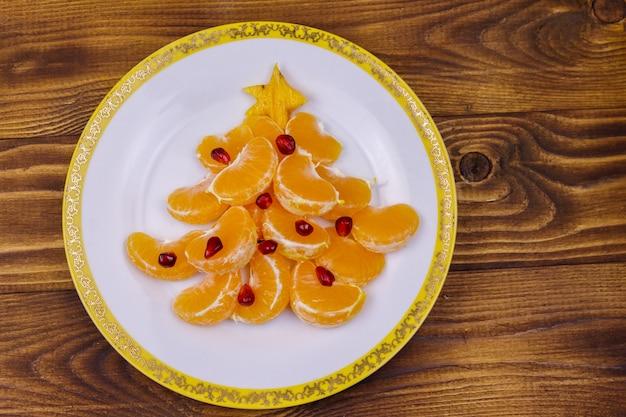 Albero di natale fatto di lobuli di mandarino e melograno sul tavolo di legno. vista dall'alto. idea creativa per i dolci delle feste di natale e capodanno. idea di cibo divertente per i bambini