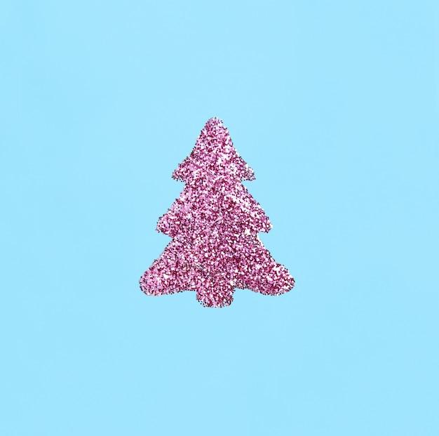Albero di natale fatto di paillettes rosa su sfondo blu concetto di natale