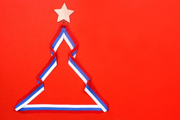 Albero di natale fatto di nastro nel colore della bandiera russa su sfondo rosso. il tricolore è un simbolo della russia. il concetto di nuovo anno