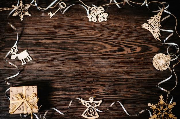 Addobbi per l'albero di natale, regalo, scatola con nastri, fiocchi di neve, campane, cervi, angelo su uno sfondo di legno marrone e strutturale. laici piatta. vista dall'alto, cornice con spazio per il testo. buone vacanze.
