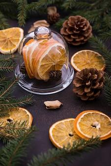Albero di natale, pigne e arance sul tavolo