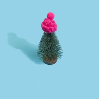 Albero di natale in berretto invernale rosa pastello su sfondo blu