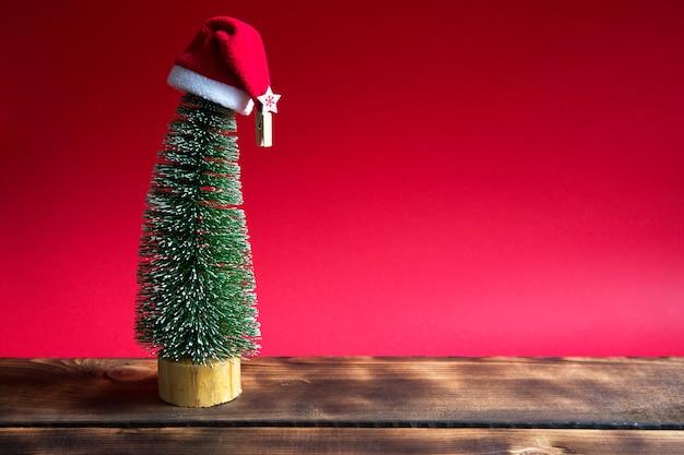 Albero di natale su uno sfondo rosso con luci di ghirlande, canna a strisce caramello