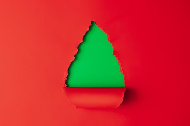 Forma ad albero di natale realizzata con carta rossa e verde. natale minimo. con copia spazio.