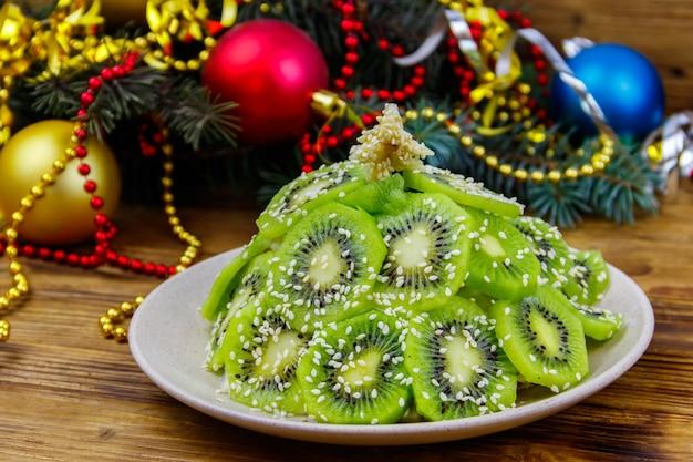 Insalata di frutta a forma di albero di natale e decorazioni di natale sulla tavola di legno. idea creativa per i dolci delle feste di natale e capodanno. idea di cibo divertente per bambini