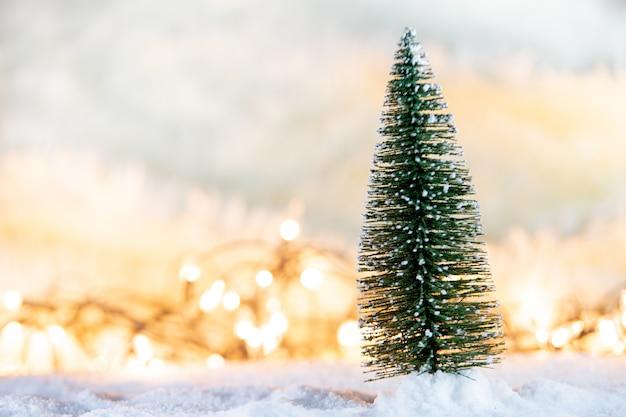 Albero di natale sulla neve con regalo e sfondi luce bokeh