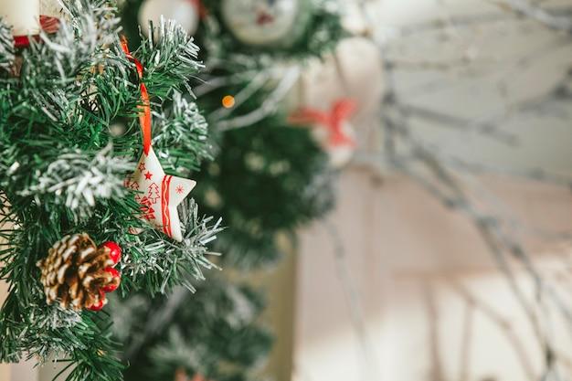 Rami di abete dell'albero di natale decorati con giocattoli di natale e coni in primo piano