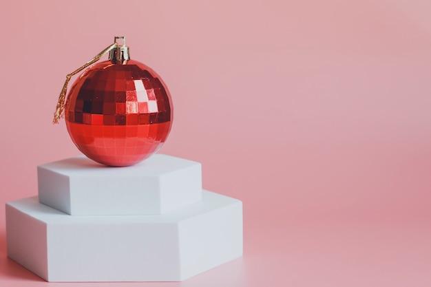 Palla rossa del giocattolo dell'albero di natale, su un podio bianco