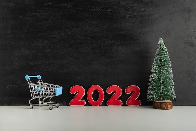 Albero di natale, carrello e numeri 2022 su sfondo scuro. acquisti per il nuovo anno. copia spazio