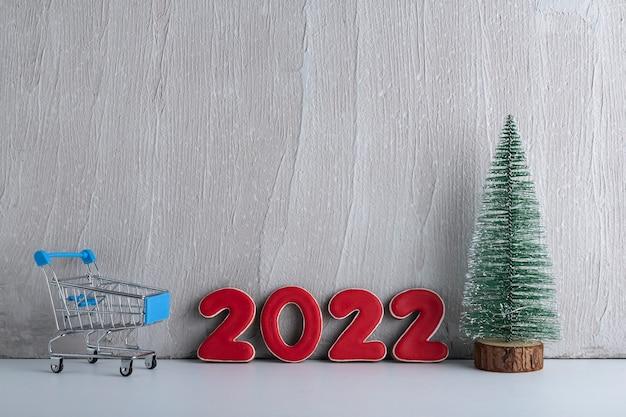 Albero di natale, carrello e numeri 2022 su sfondo chiaro. acquisti per il nuovo anno. copia spazio