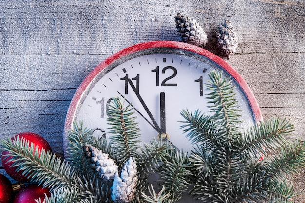 Albero di natale con le pigne e l'orologio nei precedenti della neve