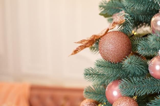 Albero di natale con giocattoli rosa in una stanza bianca di natale. casa splendidamente decorata con un albero di natale decorato per il nuovo anno