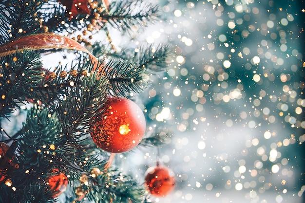 Albero di natale con l'ornamento e la decorazione rossi della palla, luce della scintilla