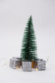 Albero di natale con piccoli regali argentati su sfondo bianco con un posto per il testo
