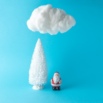 Albero di natale con piccolo babbo natale sotto la nuvola di cotone