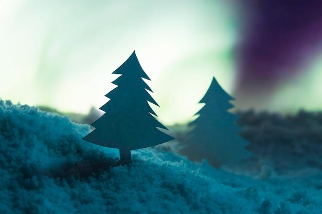 Albero di natale con neve e aurore boreali