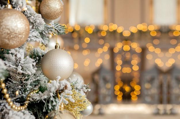 Albero di natale con giocattoli e neve decorativa per un felice anno nuovo sullo sfondo di bokee. sfondo di natale oro