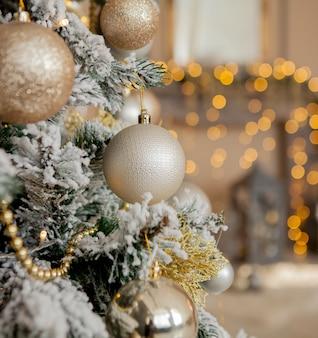 Albero di natale con giocattoli e neve decorativa per un felice anno nuovo su sfondo di bokee. sfondo di natale oro