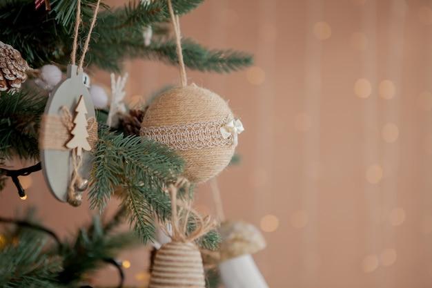 Albero di natale con giocattoli e neve decorativa per un felice anno nuovo su sfondo di bokee.