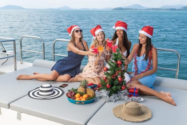 Albero di natale sullo yacht. quattro ragazze festeggiano il natale su uno yacht