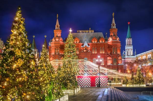 Alberi di natale in piazza manezhnaya e il museo storico con illuminazione notturna