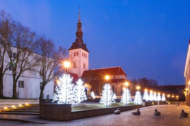 Alberi di natale e la chiesa di san nicola nella città vecchia medievale, tallinn, estonia