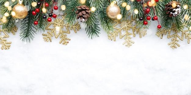 Decorazione superiore di natale con fiocchi di neve e coni di palle su sfondo di neve