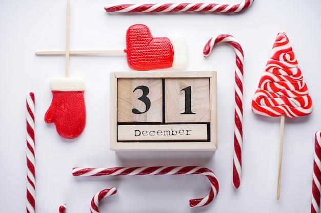 Calendario in legno stile vintage di natale con caramelle di natale su grigio. natale piatto composizione laica.