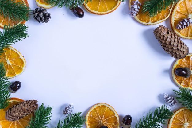 Sfondo bianco natale con posto per testo, rami di abete, arance secche, ghiande e coni innevati attorno ai bordi