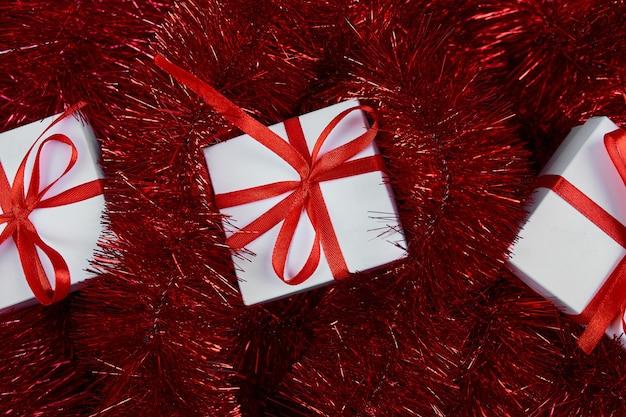 Scatola regalo bianca natalizia su sfondo rosso tinsel decorazioni abbondanti vista dall'alto piatta dall'alto
