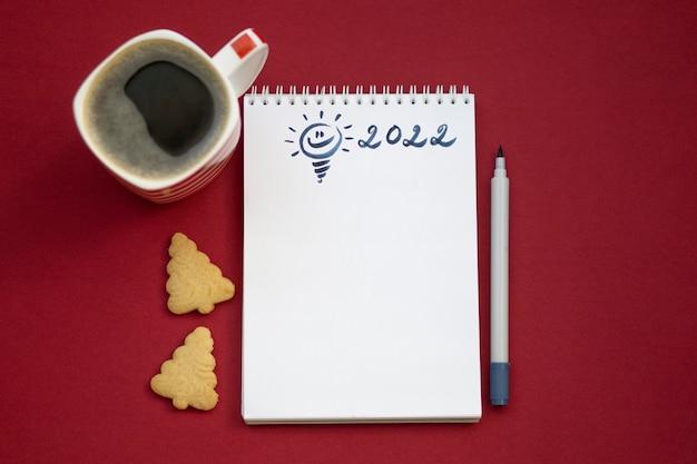 Lista dei desideri di natale 2022 o lettera a babbo natale su sfondo rosso di carta colorata. decorazione festiva, ghirlanda di natale, ramo di albero di natale. disposizione piatta. vista dall'alto.