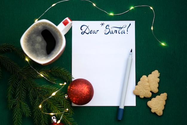 Lista dei desideri di natale 2022 o lettera a babbo natale su sfondo di carta colorata verde. decorazione festiva, ghirlanda di natale, ramo di albero di natale. disposizione piatta. vista dall'alto.