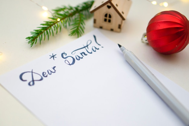 Lista dei desideri di natale 2022 o lettera a babbo natale su uno sfondo di carta di colore chiaro. decorazione festiva, ghirlanda di natale, ramo di albero di natale. disposizione piatta. vista dall'alto.