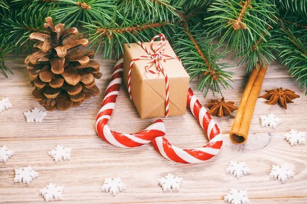 Natale con i rami dell'albero di natale, le pigne, i dolci del bastoncino di zucchero, i regali, il fiocco di neve e le decorazioni, copyspace. tonica