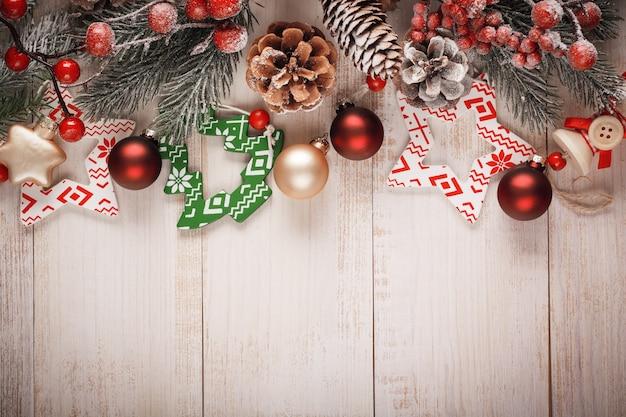 Natale con rami di abete, pigne e bacche, giocattoli natalizi in legno e vetro